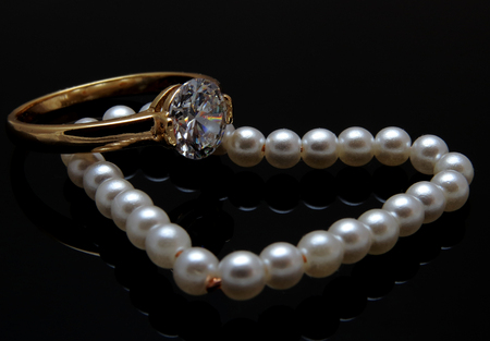 diamond necklace: Pearl heart necklace lying in form of heart on a dark background. Gold ring with diamond. Stock Photo