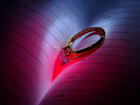 Wedding Ring and heart shaped shadow over a work book Stock Photo