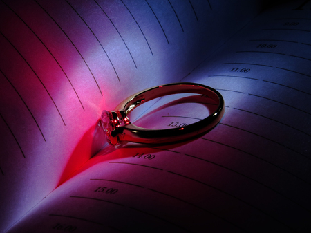 Heart shadow in light with rings on a work book.