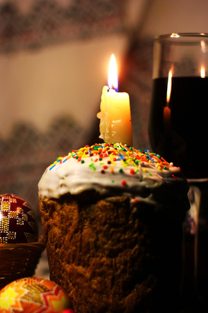 Happy Easter cupcakes, burning candle, red wine in glass,  Easter eggs on table.