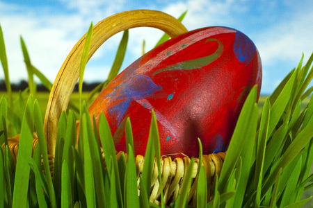 Large red decorated easter egg in basket on sky background