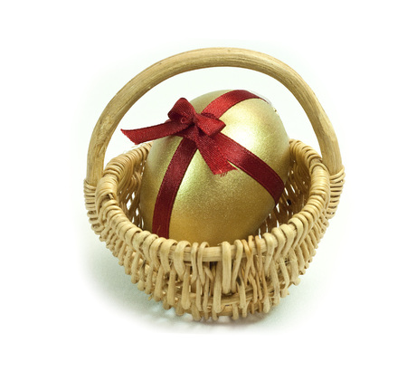 Easter Gold egg with red ribbon cross and bow in basket cart. White background isolated. Stock Photo