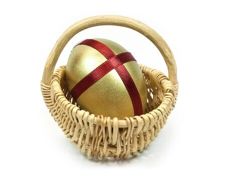 Easter Gold egg with red ribbon cross in basket cart. White background isolated.