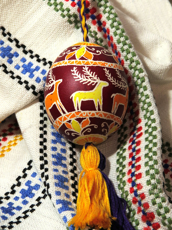 Handmade colored Easter egg on traditional Ukrainian cloth background