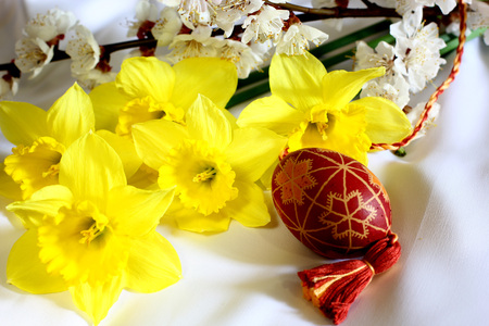 Easter picture with daffodils flowers bouquet and Easter eggs and spring of flowering tree.