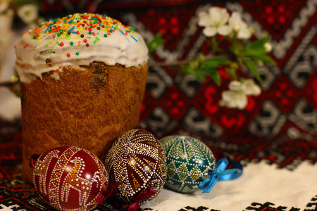 Easter decorated eggs and homemade breads on the traditional tablecloth background. Spring of flowering tree.