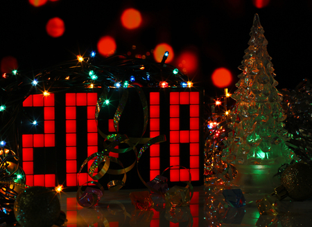 happy new year 2018 colorful greeting card with glass christmas tree on dark red bokeh lights