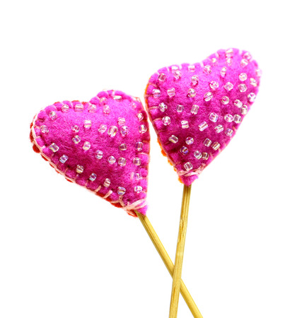 Decorative hand made two hearts isolated on white background. Sewed from a felt and decorated with beads. Beautiful congratulation card background for St. Valentine`s day. Copyspace. 版權商用圖片