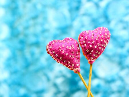 Decorative hand made two hearts on blue sky background. Sewed from a felt and decorated with beads. Beautiful congratulation card background for St. Valentine`s day. 版權商用圖片