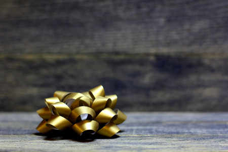 Golden bow ribbons on wooden background. Concept congratulation card background for St. Valentine`s day or birthday. 版權商用圖片