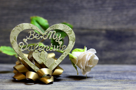 Decorative hand made heart and rose flower on wooden background. Be My Valentine inscription. Heart of decoupage technique. Beautiful congratulation card background for St. Valentine`s day.