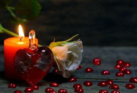 Glass heart, rose flower, Small hearts scattered on the table and burning candle on wooden background. Beautiful congratulation card background for St. Valentine`s day. Copyspace. Stock Photo
