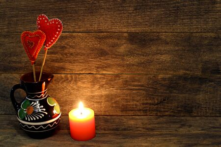 Decorative hand made hearts in small folk style vase and burning candle on wooden background. Sewed from a felt and decorated with beads. Card background for St. Valentine`s day. Copyspace.