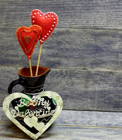 Decorative hand made hearts in small folk style vase on wooden background. Crafts from felt decorated with beads and decoupage. Beautiful card background for St. Valentine`s day. Copyspace. 版權商用圖片