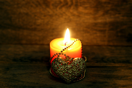 Golden heart on a chain and burning candle on wooden background. Beautiful congratulation card background for St. Valentine`s day. Copyspace.