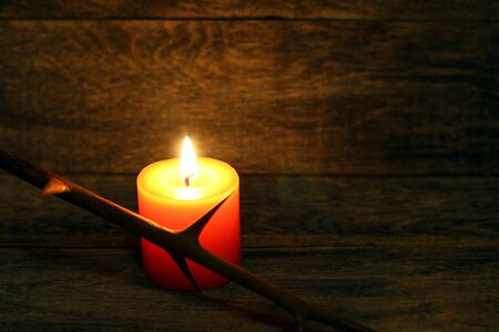 Prickly branch and burning candle on wooden background. Copyspace 版權商用圖片