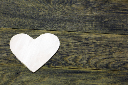 White heart on dark old wooden background. Love card for Valentines day. Concept with big copyspase for hand crafts or DIY illustration.
