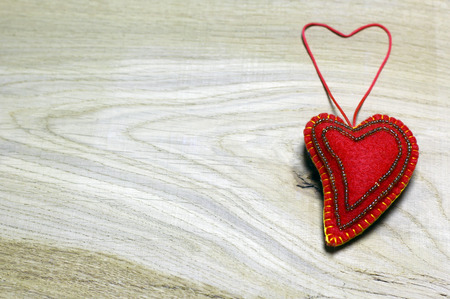 Handmade felt heart decorated with beads on wooden background. Concept with big copyspase for hand crafts or DIY illustration.