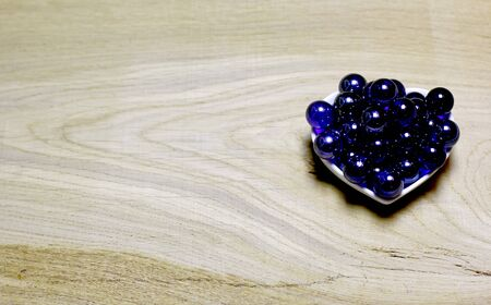 Blue glass balls on wooden background. Concept with big copyspase for hand crafts or DIY illustration.