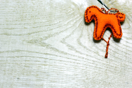 Handmade felt red color horse toy on wooden background. Concept with big copyspase for hand crafts or DIY illustration. 版權商用圖片