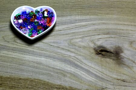 Colorful glass beads hearts on wooden background. Love card for Valentine's day. Concept with big copyspase for hand crafts or DIY illustration. 版權商用圖片 - 71383511