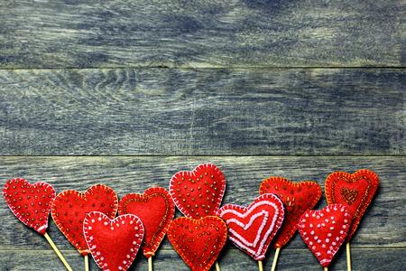 Bottom frame border of Handmade felt red color hearts on dark old wooden background. Love card for Valentine's day. Concept with big copyspase for hand crafts or DIY illustration. 版權商用圖片