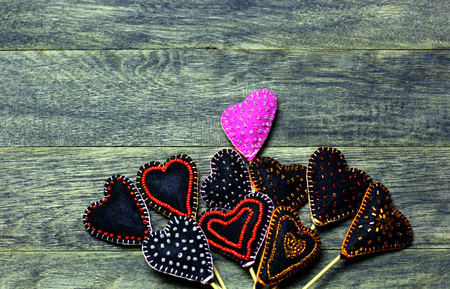 Handmade felt hearts on dark old wooden background. One heart different colors. Love card for Valentines day. Concept with big copyspase for hand crafts or DIY illustration.