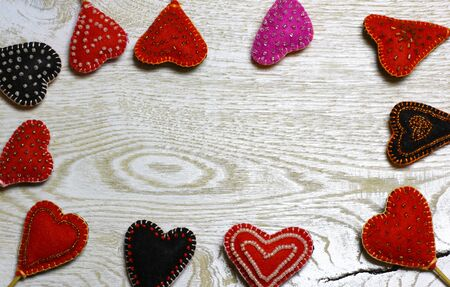 Frame border of Handmade felt hearts on light wooden background. Love card for Valentines day. Concept with big copyspase for hand crafts or DIY illustration.