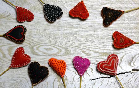 Frame border of Handmade felt hearts on light wooden background. Love card for Valentine's day. Concept with big copyspase for hand crafts or DIY illustration. 版權商用圖片 - 71254896