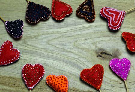 Frame border of Handmade felt hearts on light wooden background. Love card for Valentine's day. Concept with big copyspase for hand crafts or DIY illustration. 版權商用圖片 - 71254523