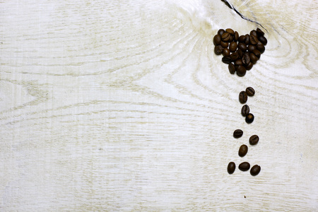 Heart of coffee beans on light wooden background. Love card for Valentines day. Concept with big copyspase for cafe or bistro advert banner.
