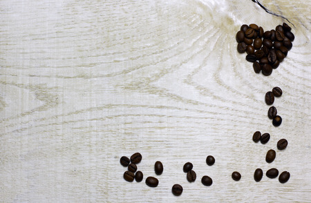 Heart and corner frame border of coffee beans on light wooden background. Love card for Valentines day. Concept with big copyspase for cafe or bistro advert banner. 版權商用圖片