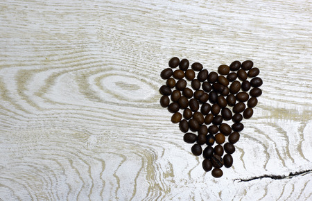 Heart of coffee beans on light wooden background. Love card for Valentine's day. Concept with big copyspase for cafe or bistro advert banner. 版權商用圖片 - 71254527