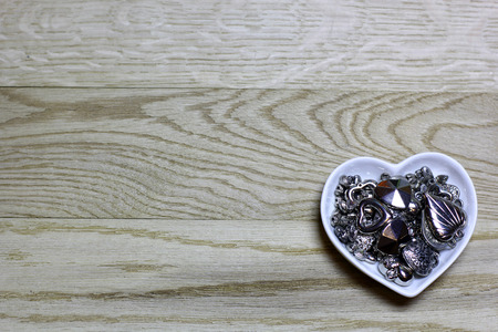 Hearts beads of metal on wooden background. Love card for Valentine's day. Concept with big copyspase for hand made crafts or DIY illustration. 版權商用圖片