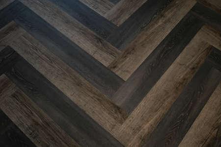 natural herringbone parquet boards, brown laminate on the floor