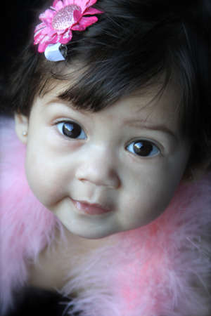 Smiling beautiful 6 month old asian baby wrapped in a bright pink boa with a flower in her hair Standard-Bild
