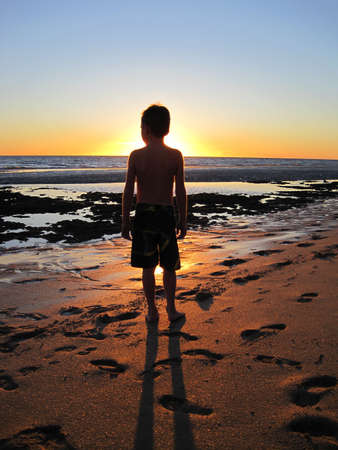 Young boy standing on the beach at low tide watching the sunset over the horizon