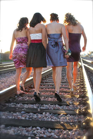Four young women walk down the railroad tracks in high heels