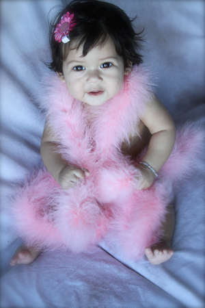 Full length photo of beautiful 6 month old baby girl wrapped in a pink boa