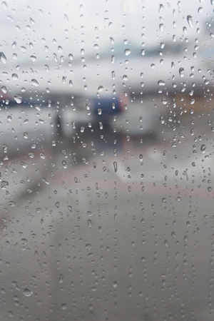 Drops Of Rain On Grey Glass Background out an airplane window with background out of focus