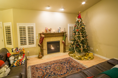 Beautiful decorated Christmas tree and fireplace a night with glowing lights and cat resting on the couch. Stock Photo