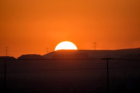 Golden sun setting beyond the hill and power lines. Reklamní fotografie