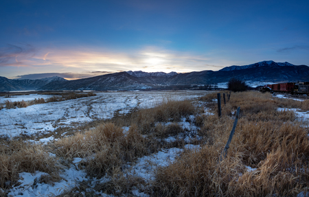 Sunset, winter landscape of a rural area with train cars in the snowy tracks and farm fields and fences in the forground of the stunning colors in the sky. Stock Photo