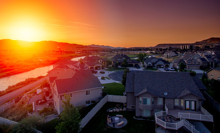 Stunning aerial view of a suburban house at sunset along the river Stock Photo