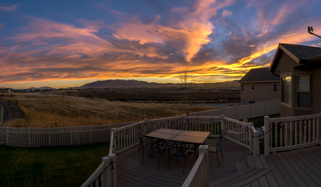 Stunningly colorful sunset or sunrise looking from the back decking of a modern home Stock Photo