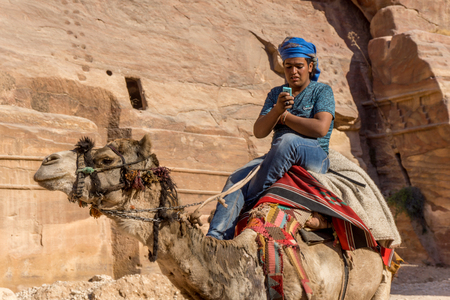 April 2017: Bedouin riding a camel while texting at Petra, Jordan shows the clash of traditional and modern life. Editorial