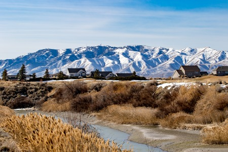 Cear skyes in a landscape of a river with snow-covered mountains n the background
