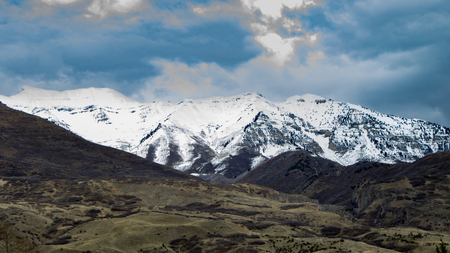 Snow-covered Rocky Mountains with foothills in the foreground and a dramatic sky Stok Fotoğraf