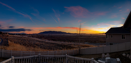 Stunningly colorful sunset or sunrise looking from the back decking of a modern home Stok Fotoğraf