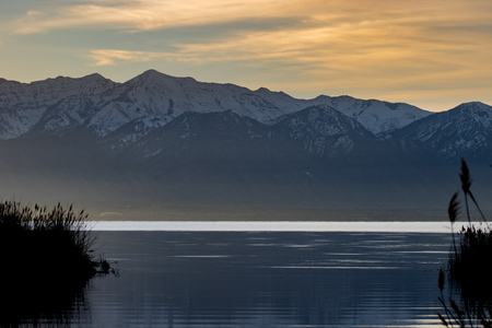 Lake with grass along the shoreline against a backdrop of snow-capped mountains during a golden sunset